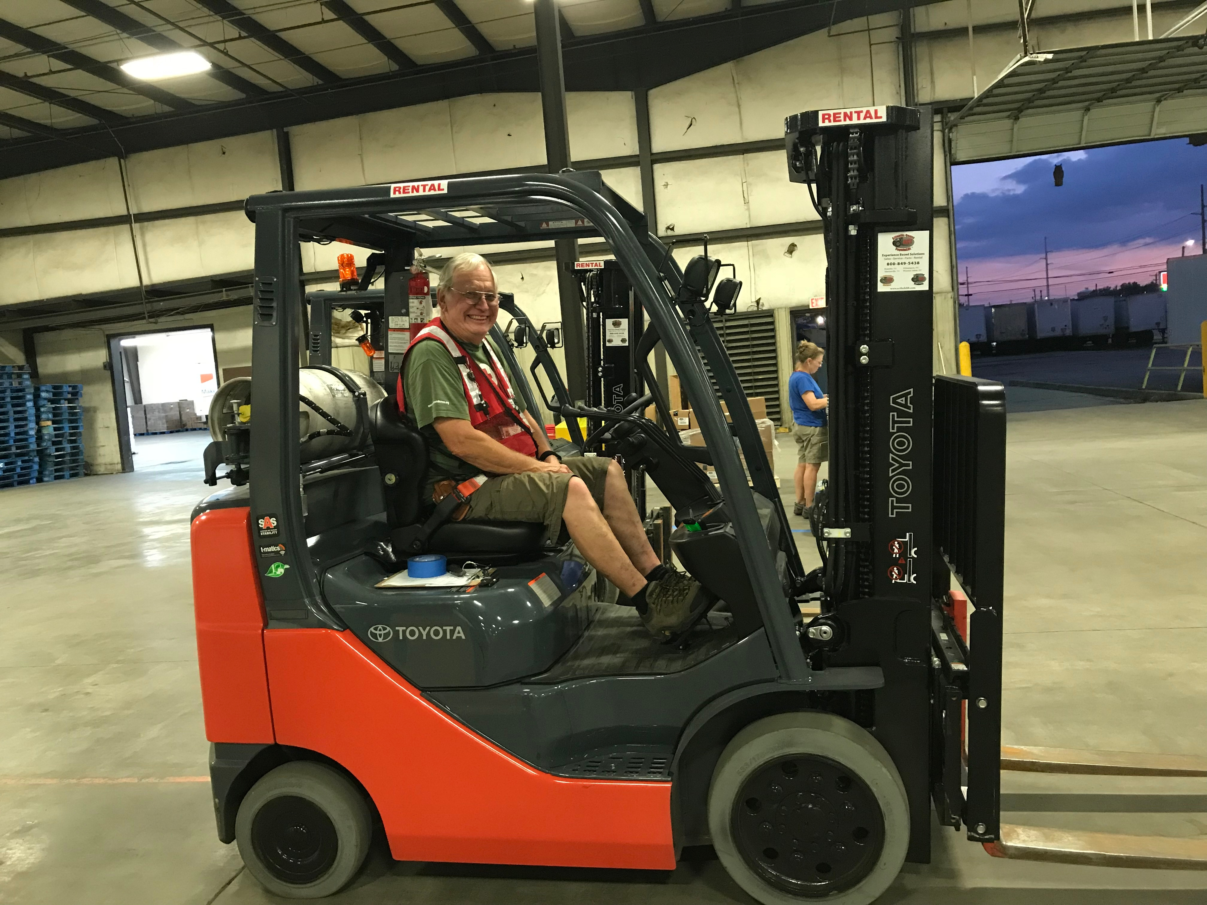 Red Cross volunteer driving a fork lift in a warehouse.