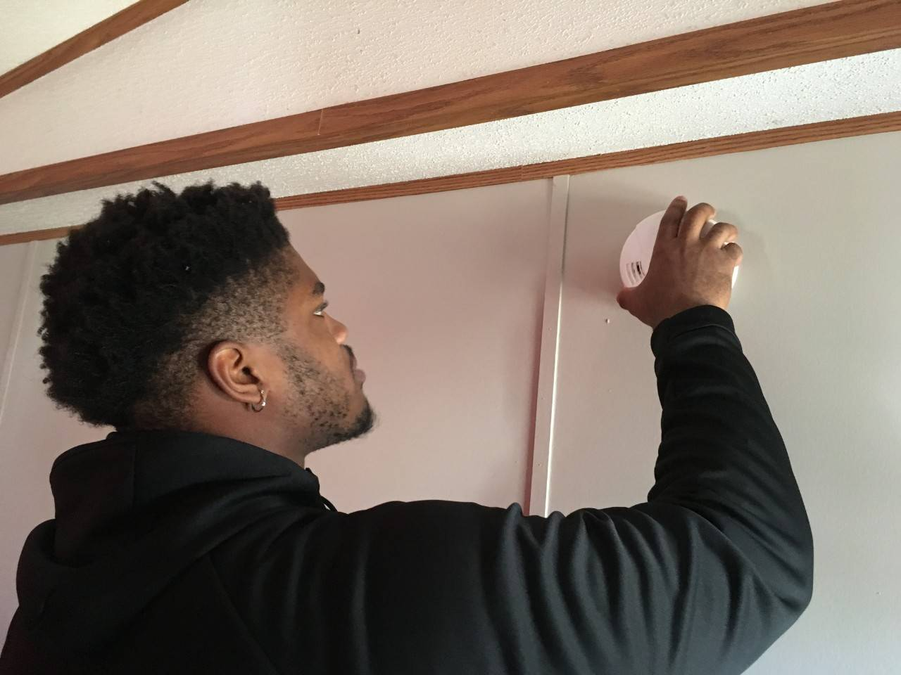 Jerard Carter (DE, Senior, Houston) installs a free smoke alarm Thursday as part of his participation in the Red Cross Sound the Alarm home fire safety event.