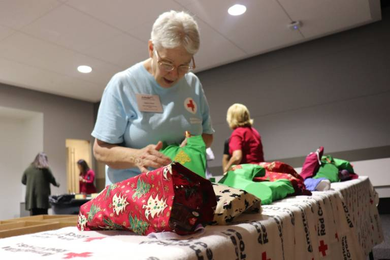 Red Cross volunteer prepares a holiday stocking