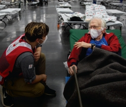 Red Cross volunteer helps man in shelter