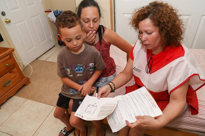 Volunteer reviews escape plan with woman and child