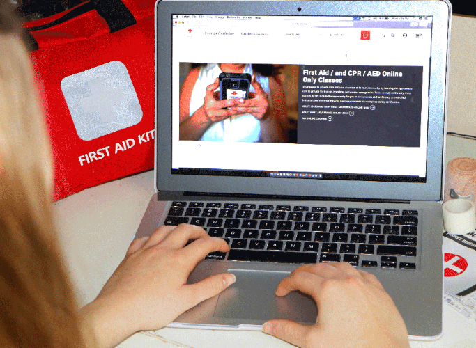Individual looking up online training courses in First Aid, CPR and AED