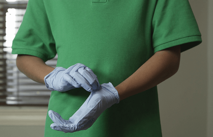 Individual practices safe removal of medical gloves.