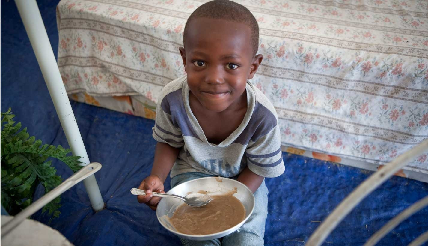 Boy in Haiti holds meal