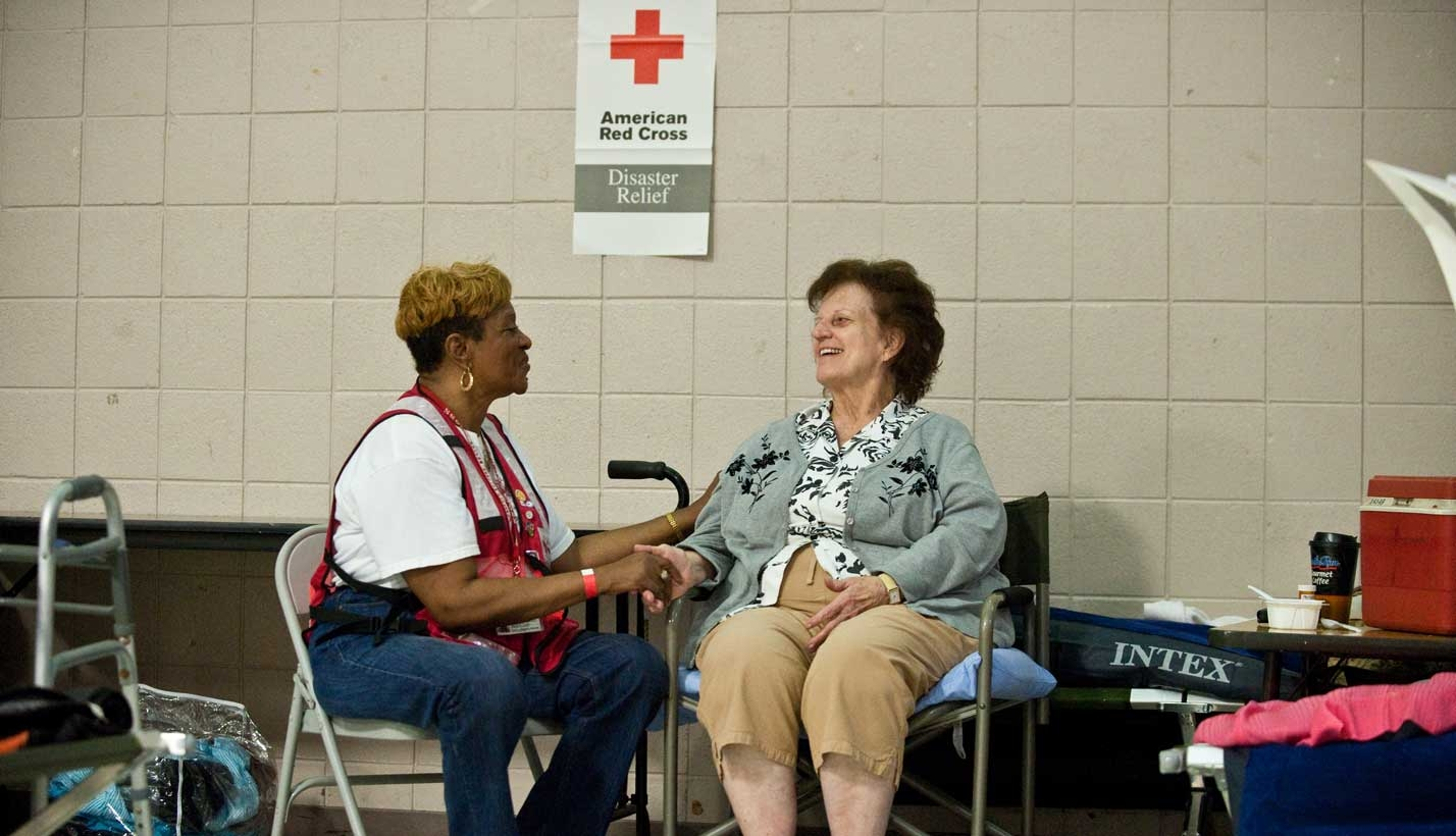 Volunteer talks to and comforts woman staying in shelter