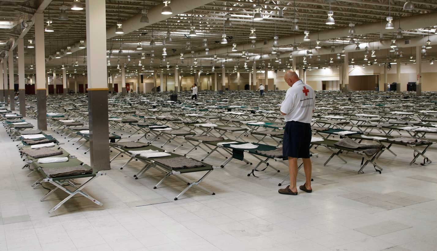 Volunteers set up cots in shelter