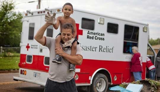 Man holds child in front of an emergency response vehicle