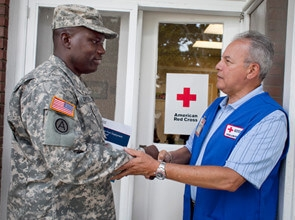 red cross worker shakes hand of military man
