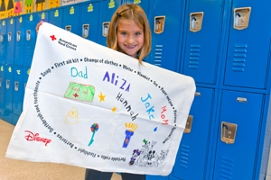 Girl holds up Pillowcase Project work she made