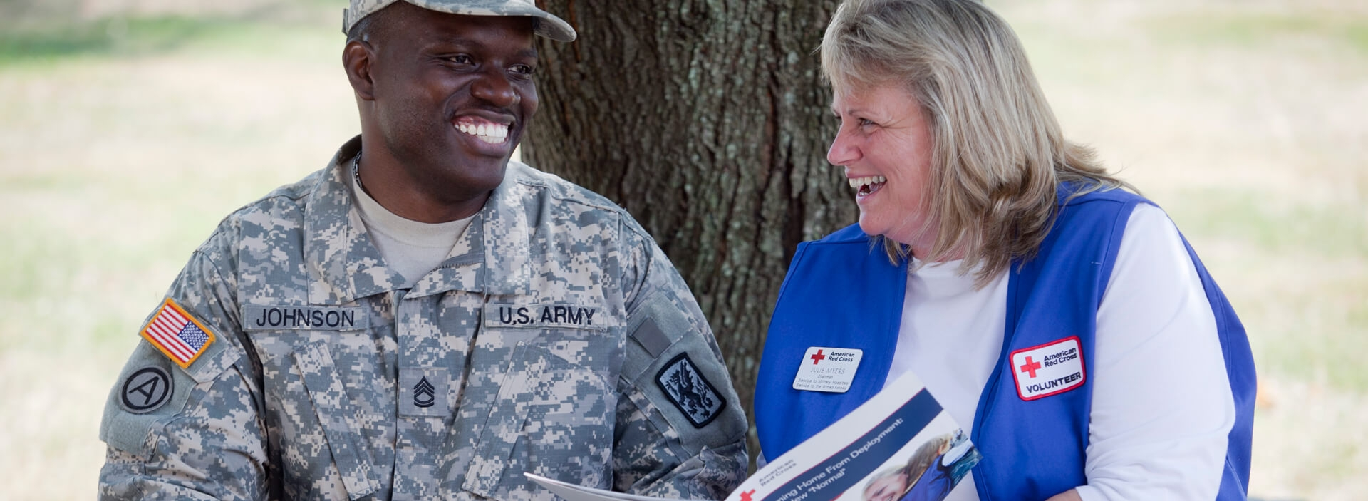 Red Cross volunteer providing information to a military personnel