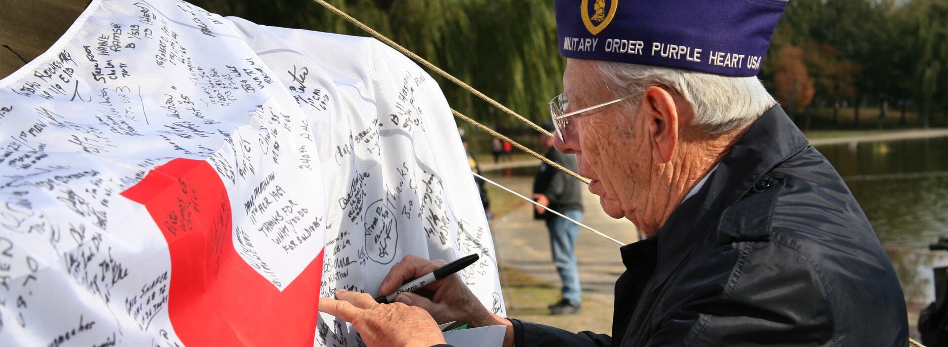 Military veteran signing American Red Cross flag