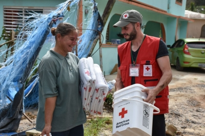 Red Cross volunteers distribute water, food and other basic necessities to families affected by Hurricane Maria.