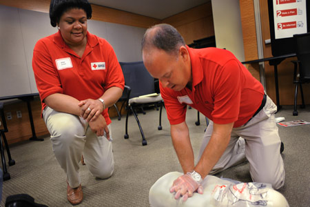 Red Cross person training a CPR class
